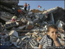 Palestinian boy sitting infront of his destroyed house